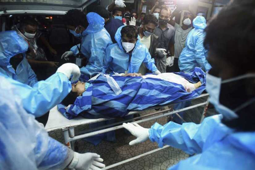 Health workers transfer an inured passenger on a stretcher to take her inside a hospital in Kozhikode.