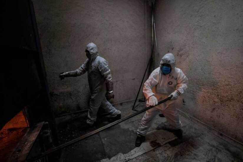 Employees wear protective gear while working at the Azcapotzalco crematorium in Mexico City.
